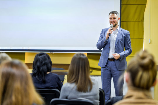 Business leader male conducts a lecture with a smile on his face during the conference. Man in stylish blue suit with microphone speaking on the background of white screen.