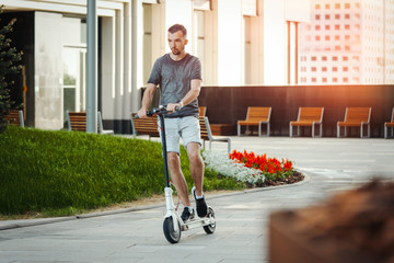 Man riding electric kick scooter next to modern buildings or commercial centres.