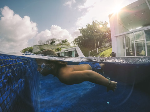 half underwater picture of a boy diving in a pool beside modern villa