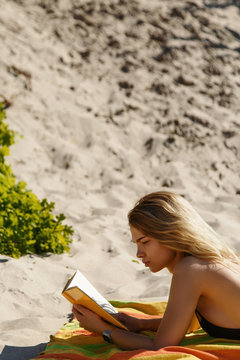 Serious young woman reading book on beach