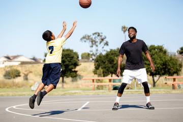 Two diverse people playing pickup basketball
