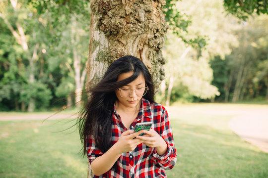 Young asian woman using phone at park.