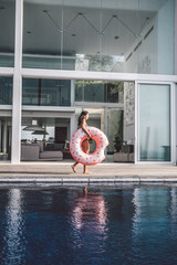 beautiful woman with inflatable pink donut walking beside a big pool