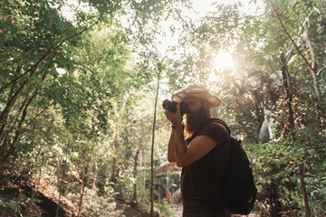 Bearded man backpacker tanking photography in the jungle.