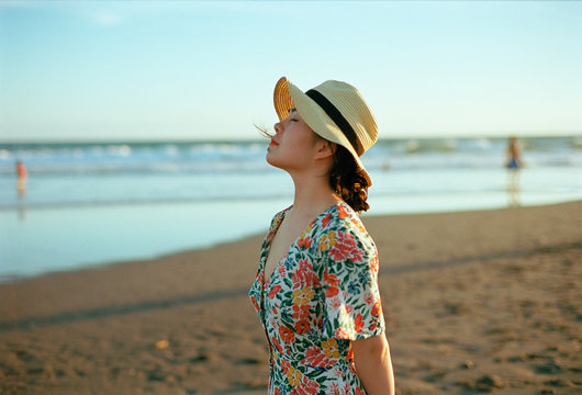 Young woman wearing hat standing on beach