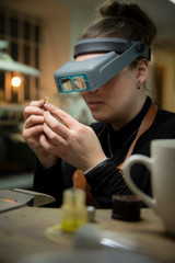 Female jeweler looking at gold through headband magnifier in workshop