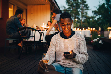 Smiling young man using mobile phone while friends in background during dinner party