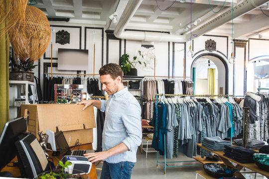 Mature sales clerk using laptop in clothing store
