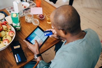 High angle view of man shopping online on digital tablet through credit card in dining room at home