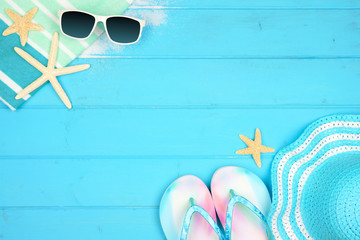 Beach accessories on a blue wood background. Summer vacation concept border with copy space. Sunglasses, sea shells, towel, flip flops and striped hat.