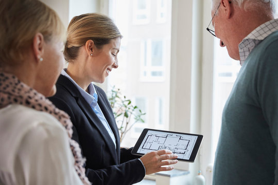 Female real estate agent showing new house blueprint on digital tablet to senior couple at home