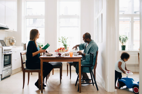 Man and woman having breakfast at table while daughter playing in living room