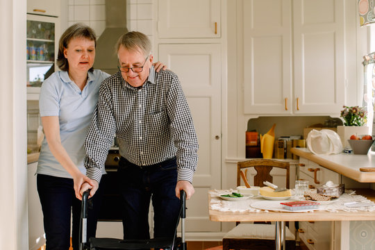 Mature female caregiver assisting retired man walking with rollator in kitchen at nursing home