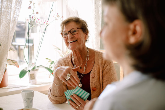 Smiling senior woman playing cards at home