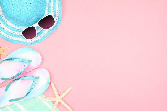Beach accessories on a pink background. Summer vacation concept side border with copy space. Sunglasses, sea shells, towel, flip flops and blue striped hat.