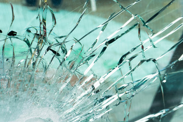 The bulletproof glass after the test, cracks and dents on the window from the bullet at the exhibition of weapons