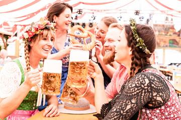 Fototapete - Gruppe von Freunden am Biertisch stoßen mit Maß an und lachen und flirten auf dem Oktoberfest