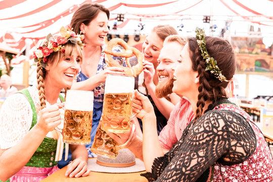 Gruppe von Freunden am Biertisch stoßen mit Maß an und lachen und flirten auf dem Oktoberfest