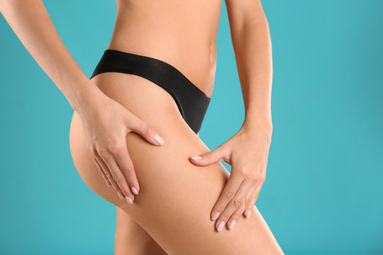 Closeup view of slim woman in underwear on color background. Cellulite problem concept