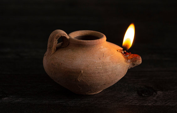 A Lit Handmade Oil Lamp from the Middle East on a Dark Table