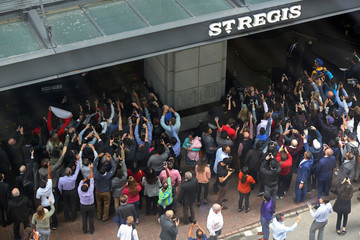 People stretch to take pictures of a bus dropping off Golden State Warriors players at their hotel in Toronto