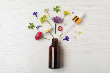 Bottle of essential oil and different flowers on white wooden background, flat lay