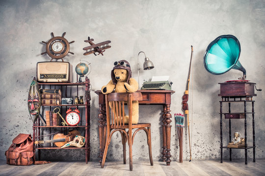 Teddy Bear toy on chair, typewriter, vintage gramophone, old books, radio, globe, binoculars, carnival mask, camera, fiddle on shelf, steering wheel, plane, travel backpack, bow. Retro style photo
