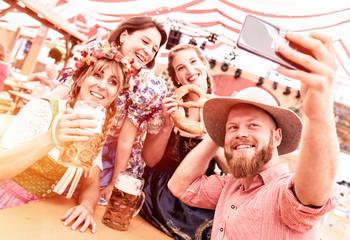 Fototapete - Freunde in Trachten mit Dirndl und Lederhose im Bierzelt am Biertisch machen Selfie Gruppenfoto