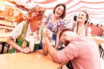 Fototapete - Freunde auf dem Volksfest im Festzelt Bierzelt beim Armdrücken und Bier trinken haben Spaß