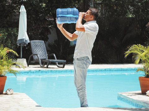 a young man wearing jeans and a shirt drinks water from a 20 liter bottle near the swimming pool. bright sun day is very hot.