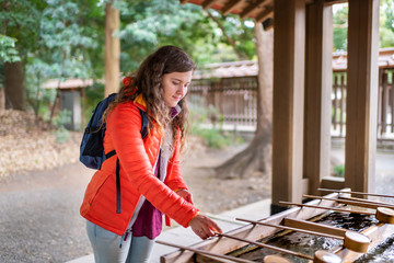Tokyo, Japan Meiji shrine entrance water purification fountain with tourist foreign woman girl person during spring placing ladle Wall mural