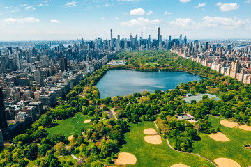 Central Park aerial view, Manhattan, New York. Park is surrounded by skyscraper. Beautiful view of the Jacqueline Kennedy Onassis Reservoir in the center of the park.