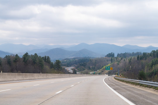 Smoky Mountains near Asheville with cloudy sky and forest trees on South 25 highway road and sign Burnsville and Spruce Pine