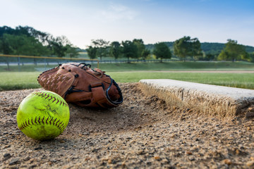 Worn softball and glove on pitchers mound on early morning springtime