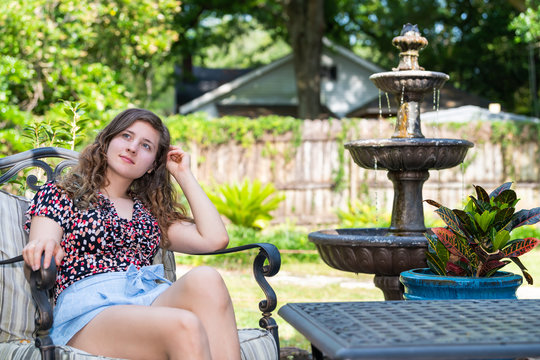 Young woman smiling looking up sitting on patio chair in outdoor spring garden in backyard of home with water fountain and table plants leaning back