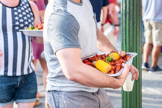 New Orleans, USA Louisiana city town with people eating seafood lobsters holding trays