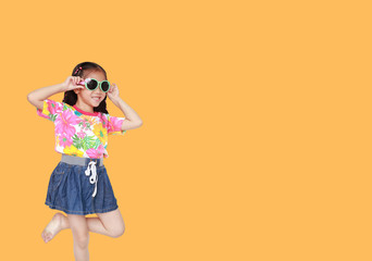 Beautiful little Asian kid girl wearing a flowers summer dress and sunglasses isolated on orange background with copy space. Summer and fashion concept.