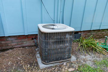 Old Air conditioner system next to home in need of maintenance