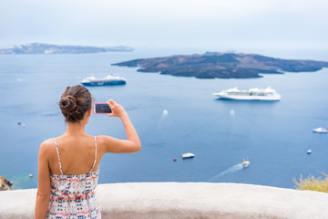 Wall Mural - Europe cruise vacation summer travel tourist woman taking picture with phone of Mediterranean Sea in Santorini, Oia, Greece, with cruise ships sailing in ocean background.