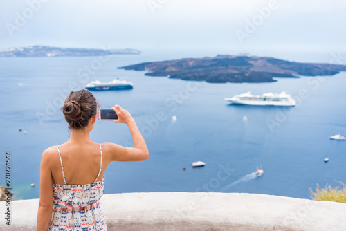 Wall mural Europe cruise vacation summer travel tourist woman taking picture with phone of Mediterranean Sea in Santorini, Oia, Greece, with cruise ships sailing in ocean background.