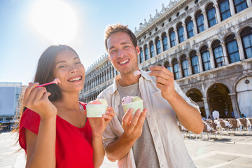Wall Mural - Happy couple tourists eating gelato ice cream on San Marco Square in Venice, Italy, Multiracial Asian woman Caucasian man on summer travel vacation eating italian food.