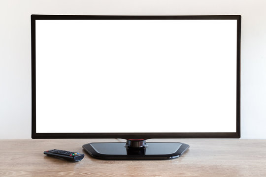 Black tv with remote control on wooden table at gray wall. Empty place for text, photo image on white screen.