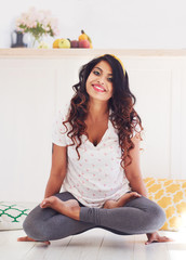 beautiful young woman doing Kukkutasana Yoga (Cockerel pose) at home