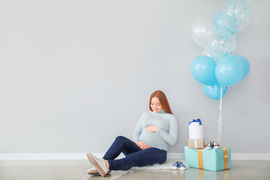 Beautiful pregnant woman with baby shower gifts near light wall