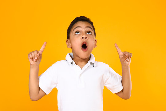 Portrait of cute little boy pointing at something on color background