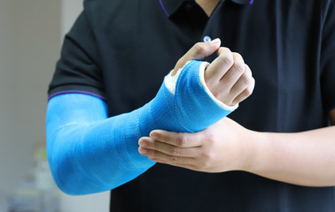 Closeup of asian man's arm with long arm plaster, fiberglass cast therapy cover by blue elastic bandage after sport injury.  Wall mural