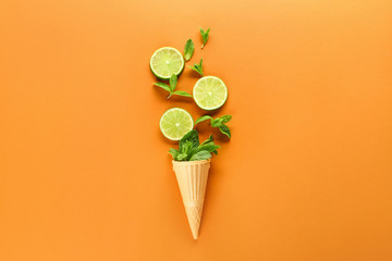 Waffle cone with fresh lime and mint leaves on color background