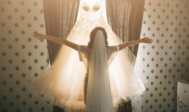 Beautiful bride looking at her wedding dress. Girl holding her clothes near the window in the morning.