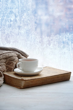 Cup of tea, books and sweater on background of winter window. sweater weather, cozy home, winter season background. concept of home comfort in cold snowy weather. copy space
