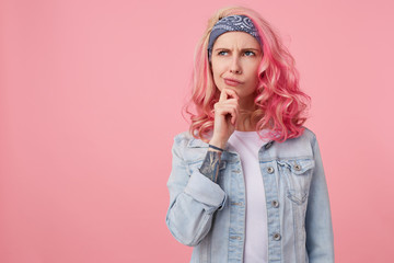 Young thinking nice woman with pink hair, stands over pink background copy space, looks up thoughtfully and touches the cheek with his finger, wears a white t-shirt and denim jacket.